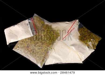Cocaine and marihuana in packages on black background