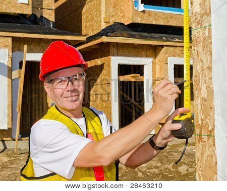 A man in a hard hat standing in front of an house at sunny day holding a measure tape in his hand.
