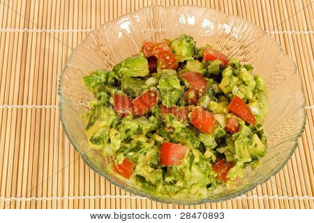 Bowl of Guacamole on a bamboo mat