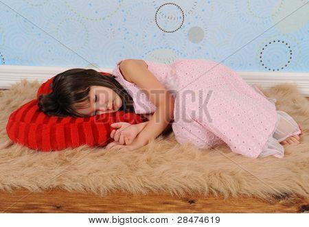 süße kleine Mädchen schlief auf herzförmige Kissen