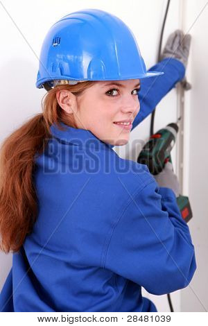 Female electrician with a power drill