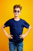 Portrait of a boy in casual clothes on a yellow background in the Studio. Childhood, kids. Casual st poster