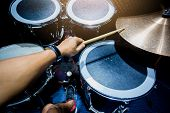 Man Playing The Drum Set With Wooden Drumsticks In Music Room poster