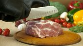 Chef With Black Gloves Takes A Knife And Regulates A Piece Of Raw Juicy Meat Lying On A Round Wooden poster