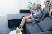 Upset Woman Eating Ice Cream While Siitng On Couch At Home Alone poster