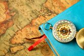 Close Up View Of Compass And Book On Vintage Old Map Background poster