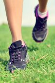 Running shoes girl jogging on grass on trail run exercising in summer park outdoor. Footwear, closeu poster
