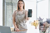 Young confident woman in workwear showing smartphone with advert of floral shop on screen poster