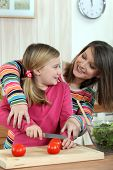 stock photo of teen pony tail  - A mother teaching her daughter how to cook - JPG