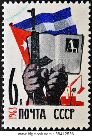 USSR - CIRCA 1963: A stamp printed in Russia shows Cuban flag hands with gun and book circa 1963