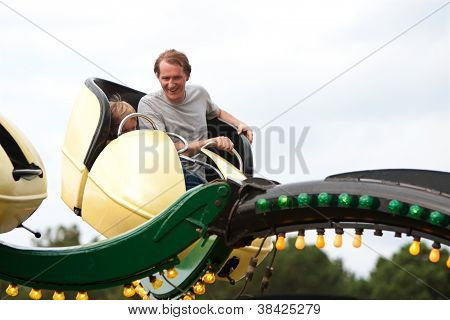 Man And Boy Enjoy Fast Moving Carnival Ride