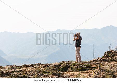 Art Fotografen mit Digitalkamera oben auf dem Berg