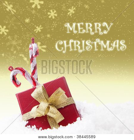 Candy cane and red box of christmas greeting on gold
