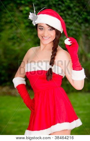 Beautiful young woman in santa suit on the garden
