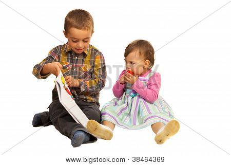 Boy Teaching Toddler Girl About Book