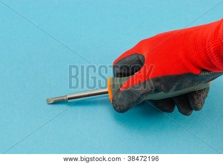 Hand With Orange Gloves Hold Screwdriver On Blue
