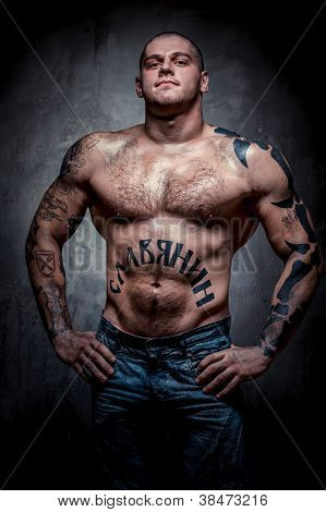 Muscular Young Man With Many Tattoos Posing Over Grey Background