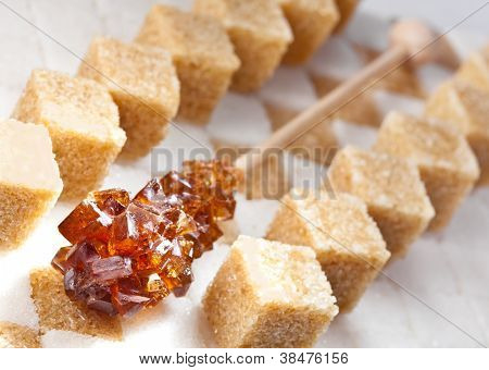 Cubes of not refined reed sugar and candy brown sugar lie on pieces of white sugar