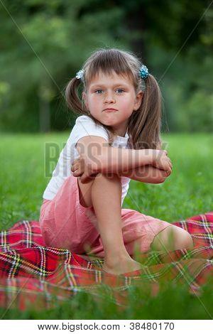 Retrato de menina valentão sentado na manta de grama
