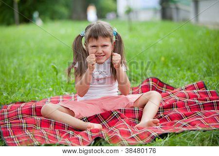 Little Irritated Girl Preschooler Sitting On Plaid And Grass