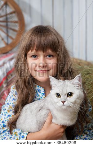 Portrait Of Sincere Girl Villager With Cat On Hands In Barn