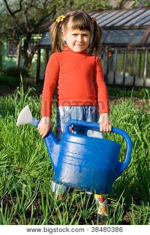 Little Girl With Watering Can On The Vegetable Garden
