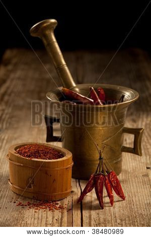 Cayenne Pods In Pounder And Milled Pepper On Wooden Table