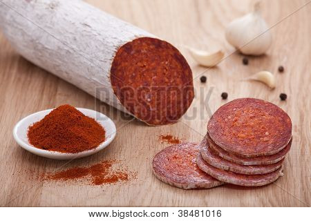 Traditional Hungarian Paprika Salami On Board With Garlic, Black Pepper