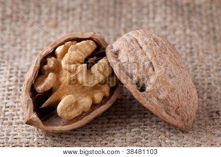 Macro Cracked Walnut, Kernel Inside, Nutshell On Sackcloth Background