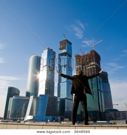 Businessman Standing With Outstretched Arms Against Skyscraper
