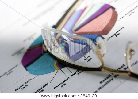 Glasses Laying On Color Diagramm. Financial Concept.