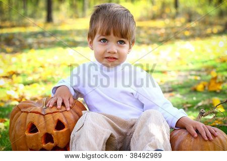 Portrait Of A Little Boy With Halloween Pumpkins