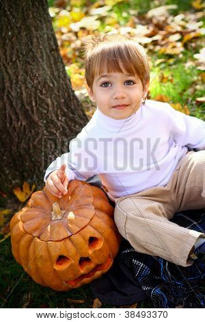 Happy Little Boy With Halloween Pumpkin Sitting Near A Tree
