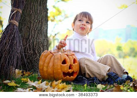 Little Boy With Halloween Pumpkin And A Broom Showing Tongue