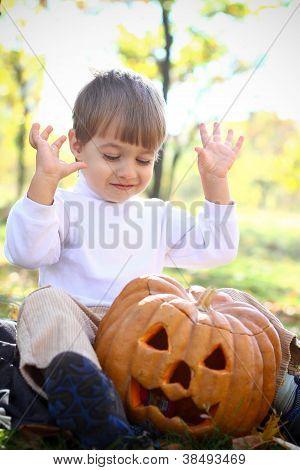Portrait Of An Enthusiastic Little Boy With Halloween Pumpkin