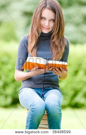 Happy Student Girl Sitting On Pile Of Books