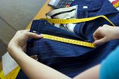 image of tailoring  - Tailor making measurements with a ruler on trousers - JPG