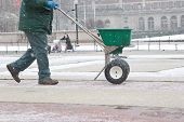 stock photo of spreader  - Man pushing a salt spreader on sidewalks in the snow