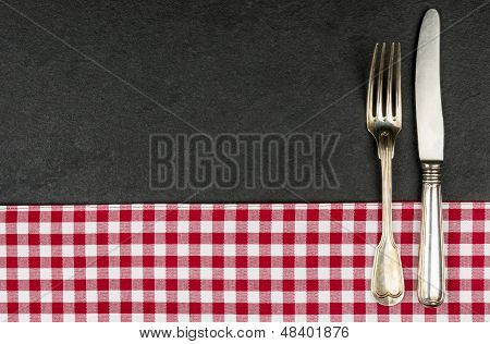 Silverware on a slate plate with a red checkered tablecloth