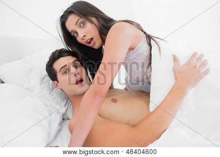 Beautiful couple surprised during the act in bed