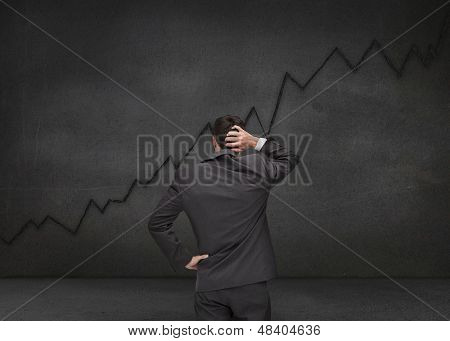 Hesitating businessman looking at black chart drawn on a black board