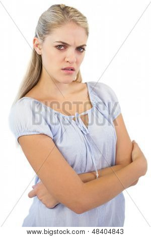 Furious blonde woman with crossed arms looking at camera