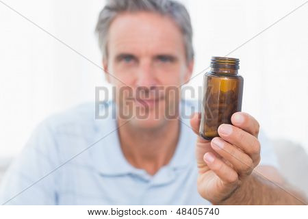 Man showing bottle of pills to camera at home