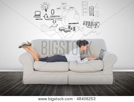 Cheerful businesswoman lying on couch and using her laptop to brainstorm