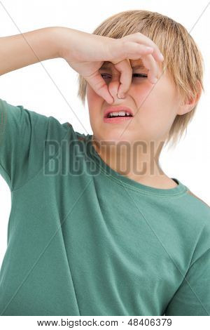 Boy pinching his nose on white background