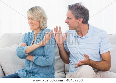 Man pleading with his wife after an argument at home on couch