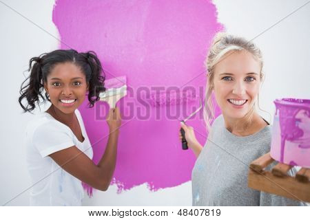 Cheerful young housemates painting wall pink in their new home and looking at camera