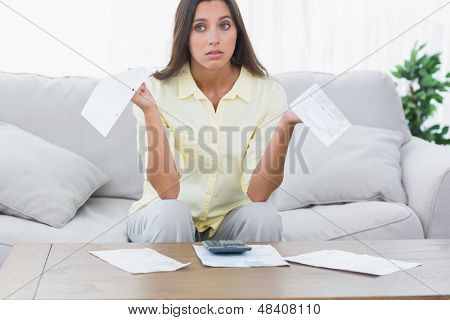 Uneasy woman doing her accounts sat on a couch