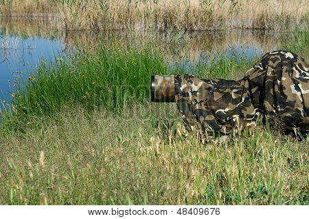 Camouflaged wild life photographer waiting for birds by lake