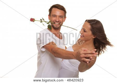 Romantic couple ballroom dancing with the man grinning as he holds a single long stemmed red rose between his teeth to celebrate Valentines day, isolated on white